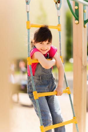 zomer, jeugd, vrije tijd en mensen concept - gelukkig meisje op de speelplaats voor de kinderen klimmen door touwladder Stockfoto