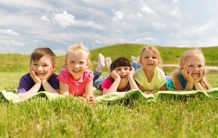 夏、子供の頃、レジャー、人々 の概念 - 毛布や屋外カバーの上に横たわる幸せな子供たちのグループ