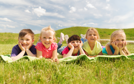 person outside: summer, childhood, leisure and people concept - group of happy kids lying on blanket or cover outdoors