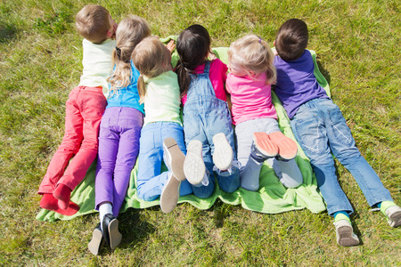 view girl: summer, childhood, leisure and people concept - group of happy kids lying on blanket or cover outdoors