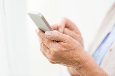 damas antiguas: la tecnolog�a, la era de la comunicaci�n y el concepto de la gente - cerca de la mujer mayor manos con el mensaje de los mensajes de texto de tel�fonos inteligentes en el hogar