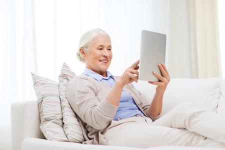 personas sentadas: la tecnolog�a, la edad y las personas concepto - mujer mayor feliz con la computadora Tablet PC en el hogar Foto de archivo