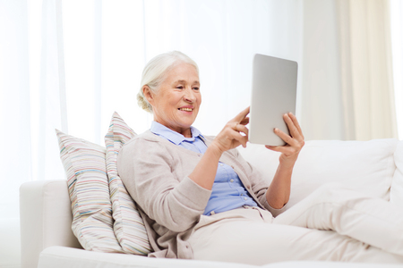 tablet computer: technology, age and people concept - happy senior woman with tablet pc computer at home Stock Photo