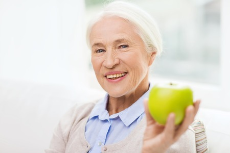 dental health: age, healthy eating, food, diet and people concept - happy smiling senior woman with green apple at home