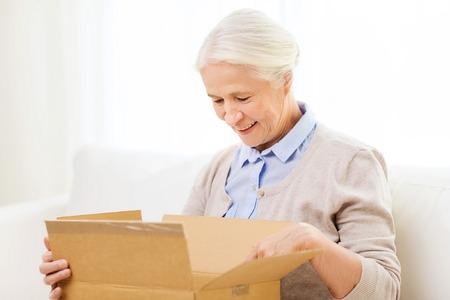 leeftijd, levering, post, de scheepvaart en de mensen concept - gelukkig lachend senior vrouw op zoek naar open pakket box thuis
