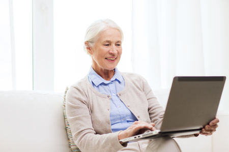 mature people: technology, age and people concept - happy senior woman with laptop computer at home