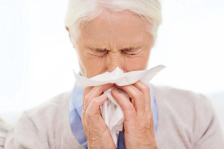 enfermos: cuidado de la salud, la gripe, la higiene, la edad y las personas concepto - mujer mayor enferma que sopla la nariz a la servilleta de papel en casa Foto de archivo