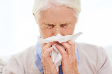 health care, flu, hygiene, age and people concept - sick senior woman blowing nose to paper napkin at home Banco de Imagens
