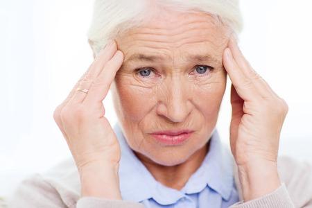 cuidado de la salud, el dolor, el estrés, la edad y el concepto de la gente - la cara de la mujer mayor que sufre de dolor de cabeza