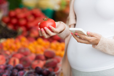 woman eating fruit: sale, shopping, food, pregnancy and people concept - close up of pregnant woman with smartphone and tomato choosing vegetables at street market
