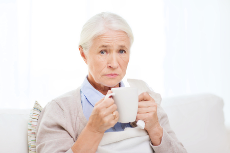 drinking problem: health care, flu, cold, age and people concept - sick senior woman with paper napkin drinking hot tea at home Stock Photo