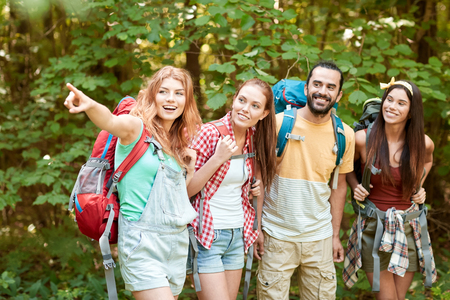 group: adventure, travel, tourism, hike and people concept - group of smiling friends with backpacks pointing finger in woods