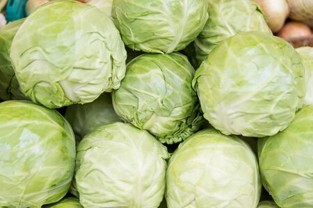 cabbages: sale, harvest, food, vegetables and agriculture concept - close up of cabbage at street market