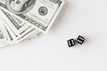 cash money: casino, gambling and fortune concept - close up of black dice and dollar cash money