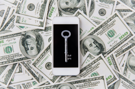 security technology: business, finance, technology and security concept - close up of smartphone with black blank screen, key and dollar money Stock Photo