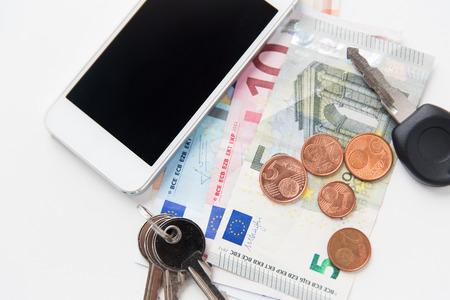 dinero euros: cosas personales y objetos concepto - cerca de smartphone, euro del dinero y las llaves en la mesa