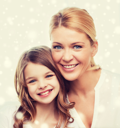 motherhood: family, childhood, motherhood, people and happiness concept - smiling mother and little girl over snowflakes background