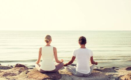 team lotus: fitness, sport, people and lifestyle concept - couple making yoga exercises sitting on pier outdoors from back Stock Photo