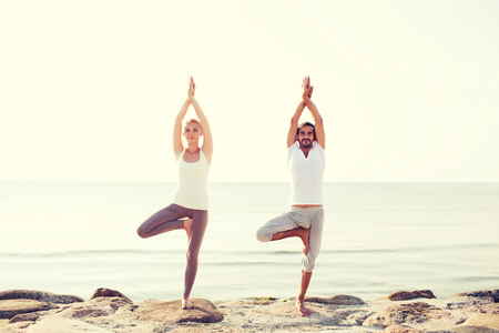 sport fitness: fitness, sport, friendship and lifestyle concept - couple making yoga exercises on beach