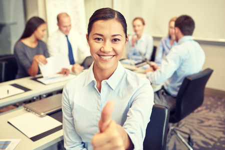 developers: business, people, gesture and teamwork concept - smiling businesswoman showing thumbs up with group of businesspeople meeting in office