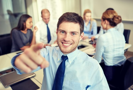 entrepreneurs: business, people, gesture and teamwork concept - smiling businessman pointing finger to you with group of businesspeople meeting in office