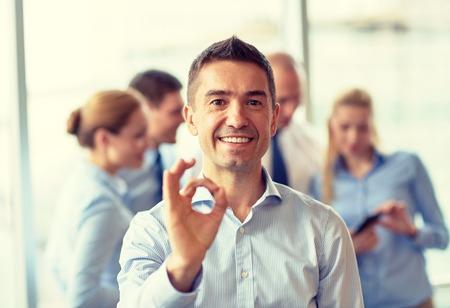 het bedrijfsleven, mensen en teamwork concept - glimlachende zakenman blijkt ok gebaar met de groep van ondernemers bijeenkomst in kantoor Stockfoto