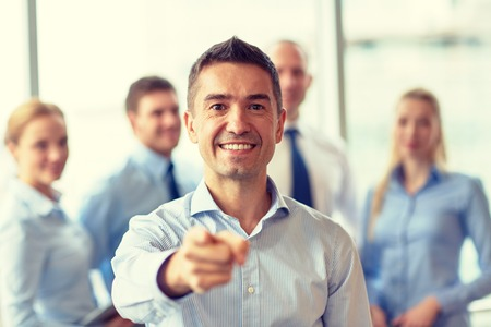 happy workers: business, people, gesture and teamwork concept - smiling businessman pointing finger to you with group of businesspeople meeting in office