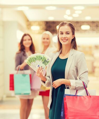 dinero euros: sale, consumerism and people concept - happy young women with shopping bags and euro cash money in mall