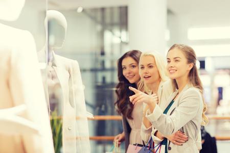 comprando: venta, el consumismo y el concepto de la gente - las mujeres j�venes felices con bolsas de la compra que se�ala el dedo a darse una ventana en el centro comercial Foto de archivo