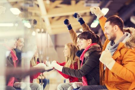 mensen, vriendschap, sport en vrije tijd concept - gelukkige vrienden kijken hockeywedstrijd of kunstschaatsen prestaties op ijsbaan Stockfoto
