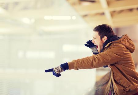 dedo: Personas, Deporte, emociones y concepto de ocio - hombre joven que apoyan partido de hockey, que señala el dedo y gritando en pista de patinaje