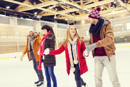amicizia: persone, l'amicizia, lo sport e il tempo libero concept - amici felici su pista di pattinaggio Archivio Fotografico