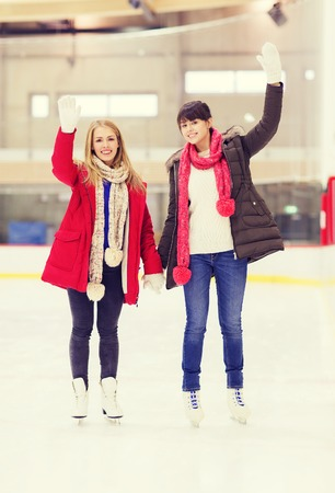 iceskates: people, women, friendship, sport and leisure concept - two happy girls friends waving hands on skating rink Stock Photo