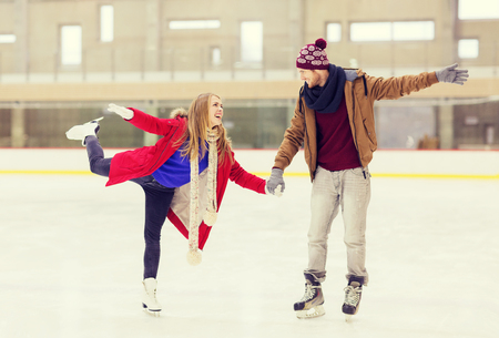 rink: people, friendship, sport and leisure concept - happy couple holding hands on skating rink