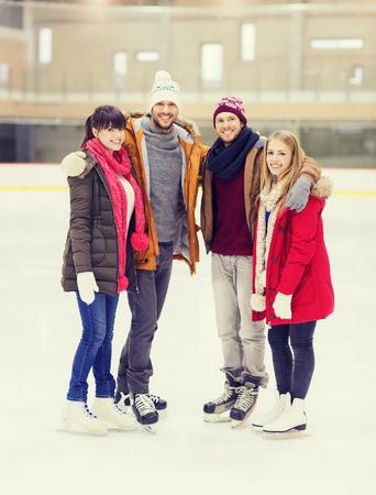 family activities: people, friendship, sport and leisure concept - happy friends on skating rink
