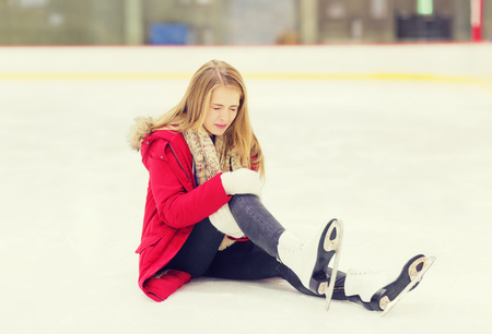 fell: people, sport, trauma, pain and leisure concept - young woman fell down on skating rink and holding to her knee