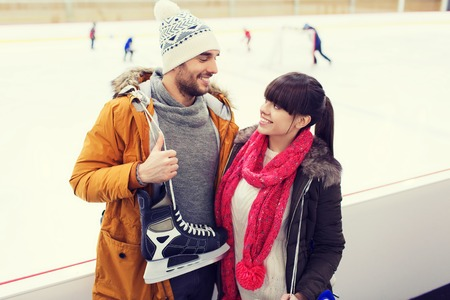 iceskates: people, friendship, sport and leisure concept - happy couple with ice-skates on skating rink
