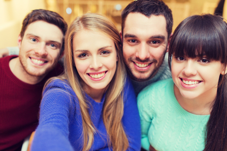 smiling: people, leisure, friendship and technology concept - group of smiling friends taking selfie Stock Photo