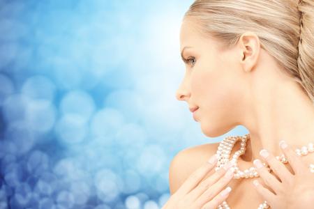 perlas: la belleza, el lujo, la gente, las vacaciones y el concepto de joyería - hermosa mujer con collar de perlas de mar o cuentas sobre luces azul de fondo Foto de archivo