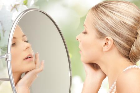 La belleza, el lujo, la gente, las vacaciones y el concepto de joyería - hermosa mujer con perlas de perlas de mar o collar que mira al espejo sobre el fondo de flor de cerezo Foto de archivo - 47664096