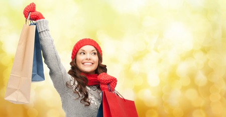 christmas shopping bag: holidays, christmas, x-mas, sale and people concept - happy young asian woman in winter clothes with shopping bags over yellow lights background