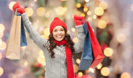 lady shopping: holidays, x-mas, sale and people concept - happy young asian woman in winter clothes with shopping bags over christmas tree lights background
