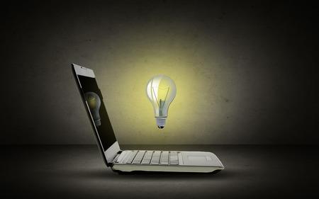 tecnologias de la informacion: technology, business, startup and idea concept - open laptop computer with lighting bulb over dark gray background