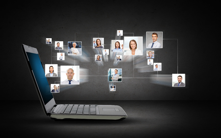 virtual community: technology, business, internet and communication concept - open laptop computer with internet contacts icons projection over dark gray background Stock Photo