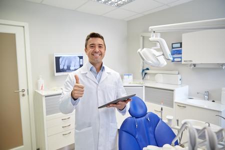 gente, medicina, estomatología y el concepto de salud - dentista feliz de mediana edad de sexo masculino en bata blanca con el ordenador Tablet PC que muestra los pulgares para arriba en la oficina clínica dental Foto de archivo