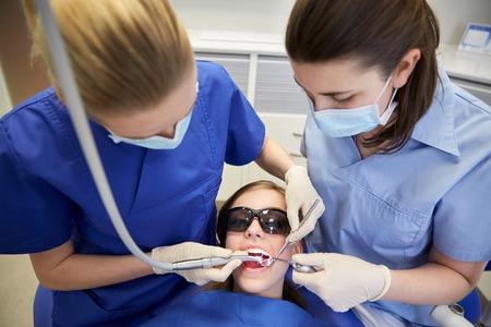 医療コンセプト - ミラー、女性歯科医、口腔医学人ドリルし、プローブの歯科オフィスで我慢の子の歯の治療