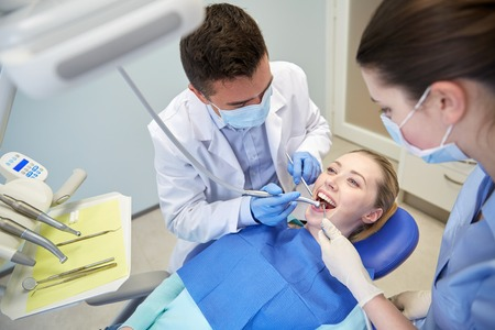 dentist drill: people, medicine, stomatology and health care concept - male dentist and assistant with dental mirror, drill and air water gun spray treating female patient teeth at dental clinic