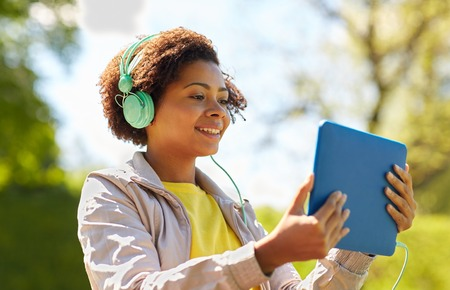 black girl: technology, lifestyle and people concept - smiling african american young woman or teenage girl with tablet pc computer and headphones listening to music or watching video in summer park