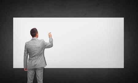 hombre escribiendo: negocio, gente, publicidad, información y concepto de la oficina - hombre de negocios escrito o dibujar algo imaginario en la tarjeta blanca de la parte posterior sobre fondo gris oscuro