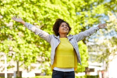 mujer alegre: la gente, la raza, el origen étnico y el concepto de retrato - feliz mujer joven del afroamericano con los brazos abiertos en el parque de verano